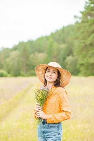 Portrait of young beautiful woman with bouquet in an orange blouse, jeans, straw hat on the hands on green background summer nature. Lifestyle, summer, rest, mood, happiness. Banque d'images - 133470282