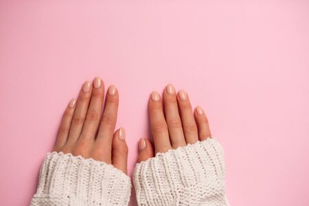 Beautiful womans hands with gentle manicure on pink background with copy space. Winter care, skin, Spa concept 写真素材