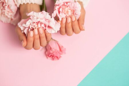 Close up beautiful pink flowers on womens hands with manicure on nails on colored background with copy space. Care, beauty, Spa, salon concept
