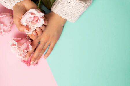Care, Spa, quality professional manicure, beauty and fashion concepts. Beautiful pink peony roses on womans hands on mint and pink background, top view, closeup, copy space