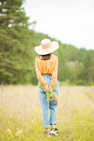 From behind. A young slender brunette woman in a beautiful hat, orange blouse and blue jeans stands with her back against the background of nature and holds wild flowers on her hand 写真素材