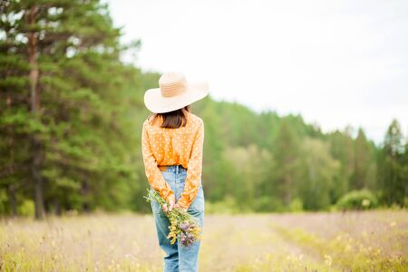 A young slender brunette woman in a beautiful hat, orange blouse and blue jeans stands with her back against the background of nature and holds wild flowers on her hand. Copy space, horizontal