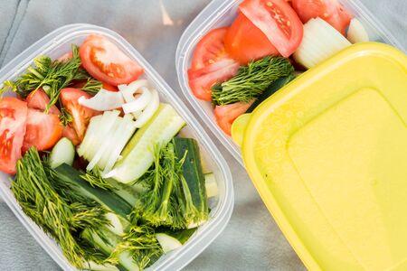 Close-up van heerlijke verse rauwe groenten uit de tuin in twee containers, bovenaanzicht. Groene komkommers, rode tomaten, dille en uien op een picknick