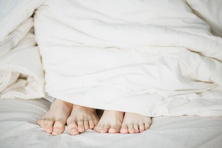 the legs of two lovers men and women pop out under the white soft fluffy clean blanket on the bed the foreground white background.