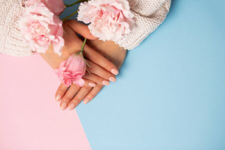 Top view of beautiful hands with manicured nails on a two tone pastel blue and pink background, closeup, copy space. Care, beauty, Spa, salon concept 写真素材