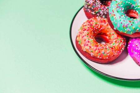 Closeup of beautiful multicolored sweet donuts in a plate on mint background with copy space. Food, restaurant, bakery concept