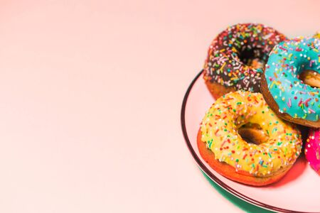 Closeup of beautiful multicolored sweet donuts in a plate on pink background with copy space. Food, restaurant, bakery concept. Selective focus