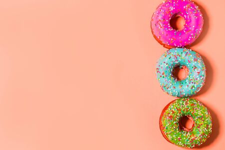 Closeup of three multicolored pink, blue and green glazed sweet donuts on coral background with copy space 写真素材