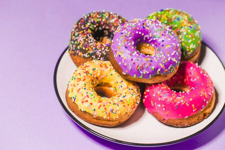 Closeup of colorful delicious fresh donuts on a purple background. Food, restaurant, bakery concept