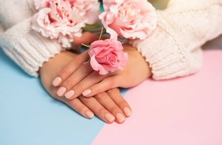Closeup of beautiful hands and flowers on multicolored pink and blue background
