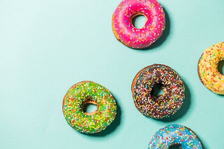 Group of glazed donuts on blue background, copy space