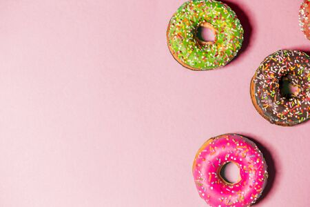Closeup of beautiful multicolored fresh donuts on paper pink background with copy space 写真素材