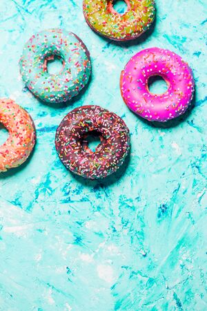 Closeup of beautiful multicolored sweet donuts in a plate on blue grunge background with copy space. Food, restaurant, bakery concept