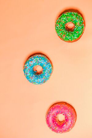 Closeup of three multicolored pink, blue and green glazed sweet donuts on color background, top view. Food, restaurant, bakery concept 写真素材