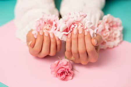 Closeup beautiful pink flowers on womens hands with manicure on nails on colored background