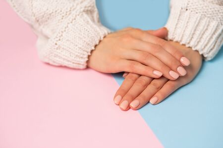 Closeup of beautiful hands with manicured nails on top of each other on a two tone pastel blue and pink background, copy space. Care, beauty, Spa, salon concept