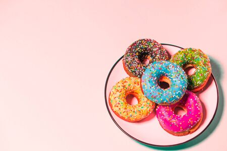 Five glazed delicious donuts in a plate on a pink background with copy space 写真素材