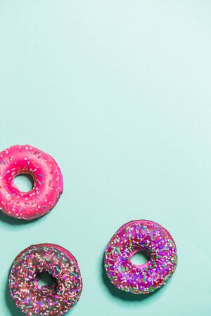 Closeup of three multicolored glazed sweet donuts on a blue background, top view, copy space. Food, restaurant, bakery concept