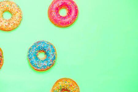 Primo piano di belle ciambelle dolci multicolori su sfondo di menta con spazio di copia. Cibo, ristorante, concetto di panetteria