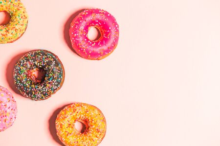 Group of glazed donuts on background pink with copy space. Food, restaurant, bakery concept