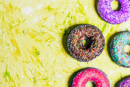 Closeup of beautiful multicolored sweet donuts in a plate on yellow grunge background with copy space, top view. Food, restaurant, bakery concept