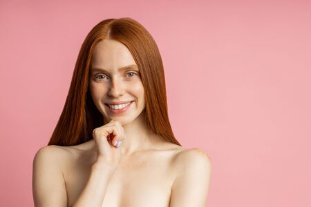 Happy young caucasian nude ginger woman with freckled clean skin touching chin, smiling pleased with result of care procedures, hair treatment posing over pink studio wall. Imagens