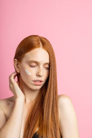Vertical shot of gorgeous sensual caucasian woman with perfect soft skin, shiny long red hair, looking down, touching neck, posing on pink background. Beauty model with cream or mask on cheek.