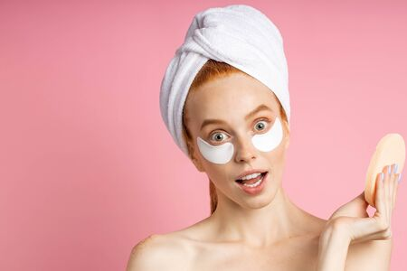 Surprised caucasian woman with naked shoulders, wearing under eye patches, holding cosmetic sponge, looking with amazed expression to camera against pink background. Skin care, beauty concept. Imagens