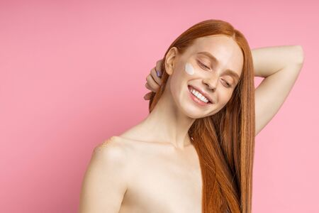Charming satisfied ginger girl with freckled skin, naked shoulders, touching her long shiny healthy hair, happy with new hair mask or conditioner, isolated over pink background. Hair treatment, spa. Imagens