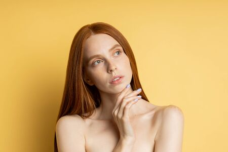 Beautiful young redhead freckled woman with clean perfect skin, without makeup touching her chin looking aside isolated over yellow background. Spa, skin care and wellness concept.