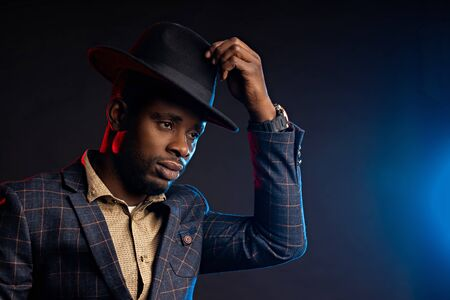 Handsome serious business African American man in hat on black background with blue and red lights in Studio, copy space Imagens
