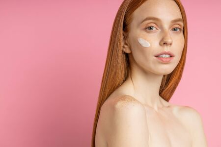 Beauty portrait of young woman with cream on cheek. Cropped shot of lovely naked redhead female using skin care product, moisturizer or lotion, posing on pink background. Imagens