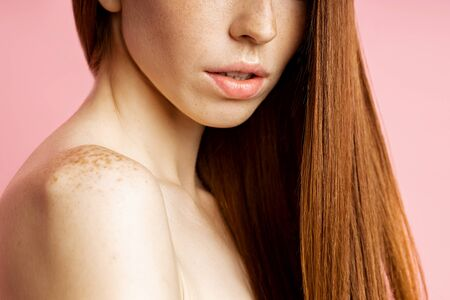 Skin care, hair treatment, spa concept. Cropped shot of sexy caucasian female model with freckled soft skin, red healthy shiny long hair, bare shoulders, sensual lips, posing on pink background.