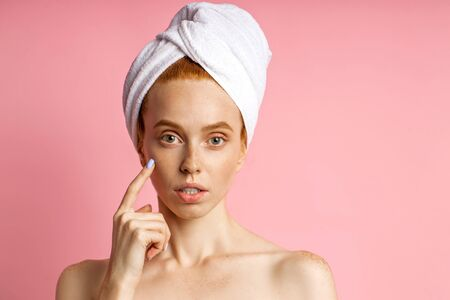 Good looking young redhead woman with smooth clean skin, bare shoulders, looking at camera, wearing towel on head, touching face with finger, applying hydratic serum or tonic after washing.