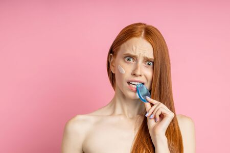 Perplexed attractive female with clean skin, long foxy hair, frowning face, looking with confused expression, biting silicone cosmetic sponge isolated on pink background. Imagens