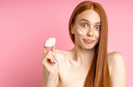 Confused young redhead woman looking at camera with puzzled expression, holding cosmetic sponge in shape of lips, shrugging shoulders. Skin care, cosmetics concept. Imagens