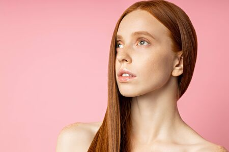 Beauty fashion portrait of naked redhead woman with perfect clean skin. Serious thoughtful girl with shiny long red hair looking aside on pink background. Youth, cosmetics, skin care concept. Imagens
