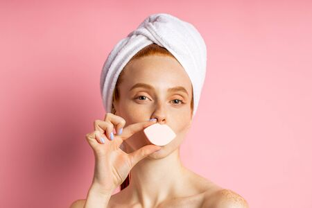 Headshot of cheerful ginger young woman with fresh clean skin, having hygienic procedures, wearing towel on head, covers mouth by cosmetic sponge in shape of lips, posing on pink background.