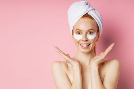 Positive caucasian woman applying collagen patches under eyes for reducing puffiness, spreading palms sideways, having happy expression, smiling broadly, standing with towel on head against pink wall.