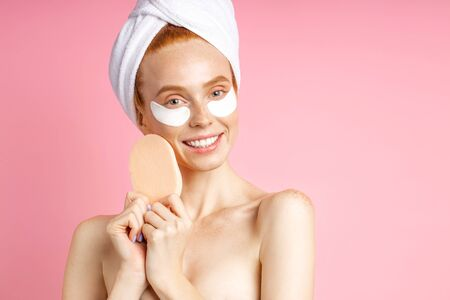Happy redhead freckled european woman with hydrogel patches under eyes for reduce puffiness, holding cosmetic sponge near face, wearing white towel on head standing against pink wall. Imagens
