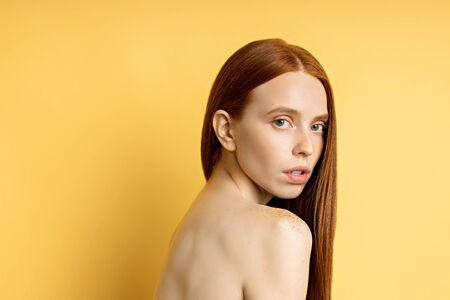 Studio portrait of sensual young woman with red long hair over yellow background. Pretty naked caucasian female model with freckled fresh clean skin. Beauty and skin care concept. Imagens