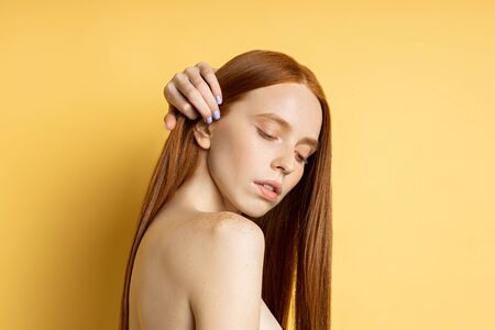 Beauty Portrait. Sexy sensual spa woman with perfect fresh skin with freckles touching her red long hair isolated on yellow background. Side view. Spa treatments and skin care concept.
