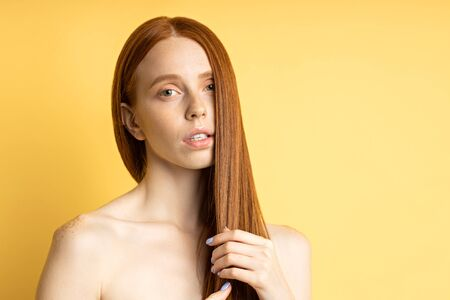 Horizontal shot of beautiful feminine young caucasian woman with freckles, clean skin touching her natural red long hair, looking sensually at camera. Beauty, hair care concept.