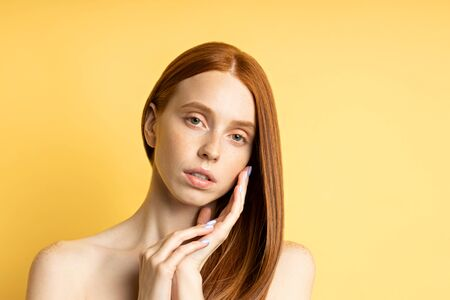 Closeup of tender relaxed caucasian young woman with red hair, bare shoulders, freckled clean skin touching cheek with hand isolated on yellow background, looking at camera. Skin care, beauty concept.