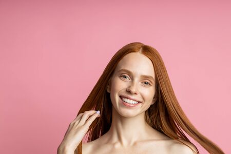 Youth, beauty, skin care concept. Joyful caucasian female model without makeup, with healthy long ginger hair, broadly smiling looking at camera with happy pleased expression. Imagens