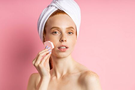 Good looking serious caucasian freckled redhead young woman with towel on head wiping face with cosmetic sponge, removing makeup, posing over pink background. Imagens