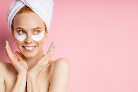 Closeup of cheerful redhead young woman applying moisturizing hyaluronic patches, biting lips, looking to side with happy expression posing over pink background with copy space. Imagens