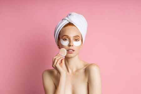 Good looking redhead freckled european woman with hydrogel patches under eyes for reduce eye bags, holding cosmetic sponge, wearing towel on head standing against pink wall. Care, wellness concept. Imagens