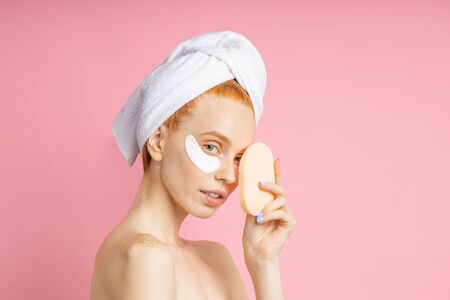 Portrait of positive ginger woman wearing collagen patches under eyes, holding cosmetic sponge near face, having skin care procedures after shower standing against pink background.