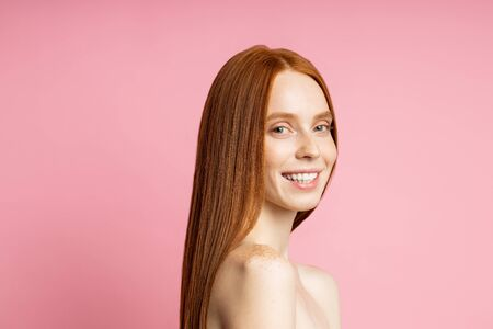 Happy attractive redhead caucasian young lady with fresh skin, without makeup, broadly smiling with perfect white teeth isolated over pink background. Spa treatments, skin, hair care.